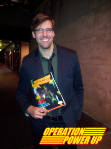 He's holding vol. 34 Nintendo Power, featuring: LoZ: ALttP since  A Link Between World's has been released in the US!